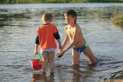 Τα παιδιά λούζουν το βράδυ στην παραλία πόλεων στοκ εικόνα