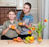 Τα παιδιά πίνουν το συμπιεσμένο χυμό από πορτοκάλι από το γ Στοκ Εικόνες