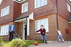 Τα παιδιά παίζουν στον κήπο δεδομένου ότι ο πατέρας κόβει το χορτοτάπητα έξω από το σπίτι Στοκ Εικόνες