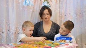 Τα παιδιά παίζουν τα επιτραπέζια παιχνίδια στον πίνακα με την οικογένεια απόθεμα βίντεο