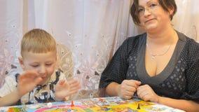 Τα παιδιά παίζουν τα επιτραπέζια παιχνίδια στον πίνακα με την οικογένεια φιλμ μικρού μήκους