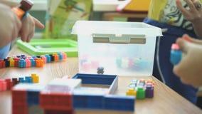 Τα παιδιά παίζουν τα διανοητικά παιχνίδια σε έναν παιδικό σταθμό φιλμ μικρού μήκους