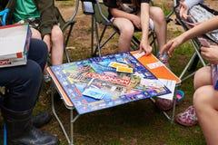 Τα παιδιά παίζουν το επιτραπέζιο παιχνίδι στο μονοπώλιο στοκ φωτογραφίες