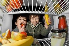 Τα παιδιά παίρνουν τα τρόφιμα από το ψυγείο Στοκ Φωτογραφία
