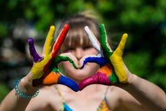 Τα παιδιά παραδίδουν τα χρώματα χρώματος κάνουν μια μορφή καρδιών, εστιάζουν στα χέρια στοκ φωτογραφίες