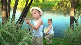 Τα παιδιά περπατούν χαρωπά μετά από το υπόλοιπο επάνω Οι αδελφοί ψιθυρίζονται μετά από να αλιεύσουν ευτυχή παιδιά μετά από να αλι φιλμ μικρού μήκους