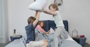 Τα παιδιά που έχουν τα μαξιλάρια παλεύουν στο κρεβάτι με τους γονείς ύπνου, πρωί της ευτυχούς οικογένειας στην κρεβατοκάμαρα φιλμ μικρού μήκους
