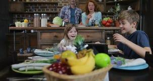 Τα παιδιά που κάθονται στο γεύμα παρουσιάζουν την αναμονή τον υπολογιστή ταμπλετών χρήσης γεύματος, ευτυχής οικογένεια στην κουζί φιλμ μικρού μήκους