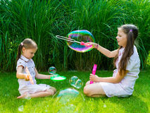 Τα παιδιά που παίζουν με το σαπούνι βράζουν ράβδος στο πάρκο σε ένα ηλιόλουστο SU Στοκ Εικόνες