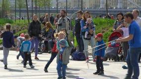 Τα παιδιά που παίζουν σε μια πόλη σταθμεύουν με τις μεγάλες σαπωνώδεις φυσαλίδες απόθεμα βίντεο