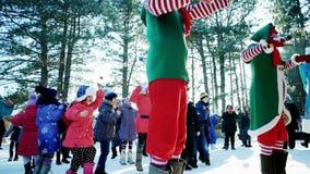 Τα παιδιά που χορεύουν, εύθυμος χορός στο χιόνι σε ένα πάρκο στο νέο φεστιβάλ έτους, εμψυχωτές παίζουν με τα παιδιά απόθεμα βίντεο