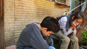 Τα παιδιά προσφύγων κάθονται κοντά σε ένα σπίτι Πόλεμος, σεισμός, πυρκαγιά, βομβαρδισμός απόθεμα βίντεο