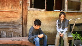Τα παιδιά προσφύγων κάθονται κοντά σε ένα σπίτι Πόλεμος, σεισμός, πυρκαγιά, βομβαρδισμός φιλμ μικρού μήκους