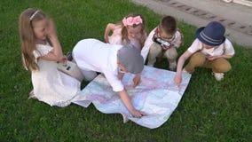 Τα παιδιά σε έναν αναδρομικό στα ενδύματα κάθονται σε μια χλόη κοντά στο παλαιό τούβλο χτίζοντας εξετάζοντας το χάρτη Τα παιδιά ψ απόθεμα βίντεο