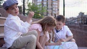 Τα παιδιά σε έναν αναδρομικό στα ενδύματα κάθονται στην οικοδόμηση των βημάτων Τα παιδιά ψάχνουν τις περιπέτειες Τα παιδιά εξετάζ απόθεμα βίντεο