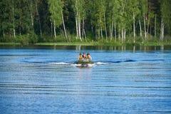 Τα παιδιά στη βάρκα μηχανών κολυμπούν στη λίμνη Στοκ φωτογραφία με δικαίωμα ελεύθερης χρήσης
