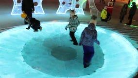 Τα παιδιά στο φωτισμένο πάγο περιβάλλουν την πυραμίδα στην πόλη πάγου τη νύχτα απόθεμα βίντεο