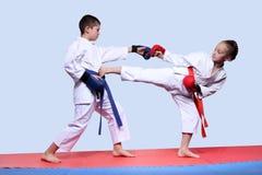 Τα παιδιά στο karategi κτυπούν το λάκτισμα και punching Στοκ Εικόνες