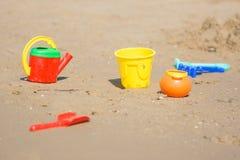 Τα παιδιά στρώνουν με άμμο τα παιχνίδια βρίσκονται στην παραλία παραλιών Στοκ Εικόνες