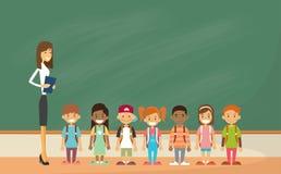 Τα παιδιά σχολείου ομαδοποιούν με την τάξη δασκάλων τον πράσινο πίνακα Στοκ εικόνα με δικαίωμα ελεύθερης χρήσης
