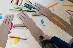 Τα παιδιά σύρουν έναν ρομποτικό βραχίονα που γίνεται με το χαρτόνι χαρτόνι Στοκ φωτογραφία με δικαίωμα ελεύθερης χρήσης