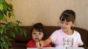 Τα παιδιά σύρουν με τα χρώματα Δύο κορίτσια επισύρουν την προσοχή τα σπίτια στον πίνακα με τα χρώματα Μια βούρτσα πλένεται σε ένα φιλμ μικρού μήκους