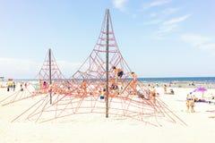Τα παιδιά το καλοκαίρι στην παραλία θαλασσίως αναρριχούνται στα σχοινιά στοκ εικόνα