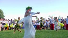 Τα παιδιά χορεύουν με τα στεφάνια στο kupala ivana διακοπών στη φύση, κορίτσια που χορεύουν στα κοστούμια υπαίθριος στο φεστιβάλ, απόθεμα βίντεο
