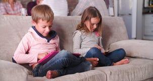 Τα παιδιά χρησιμοποιούν τις ψηφιακές συσκευές όπως οι γονείς μιλούν στο υπόβαθρο απόθεμα βίντεο