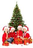 Τα παιδιά Χριστουγέννων στο καπέλο Santa με παρουσιάζουν τη συνεδρίαση κάτω από το δέντρο έλατου πέρα από το λευκό Στοκ εικόνες με δικαίωμα ελεύθερης χρήσης