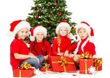 Τα παιδιά Χριστουγέννων στο καπέλο Santa με παρουσιάζουν τη συνεδρίαση κιβωτίων δώρων κάτω από το έλατο tre Στοκ Φωτογραφίες