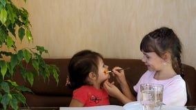 Τα παιδιά χρωματίζουν τα πρόσωπά τους με τα χρώματα Το κορίτσι χρωματίζει το πρόσωπο ενός άλλου κοριτσιού με τα χρώματα Κοκκινίστ φιλμ μικρού μήκους