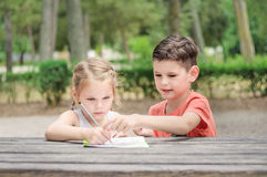 Τα παιδιά Hapy μαθαίνουν σε ένα πάρκο Ο αδελφός και η αδελφή κάνουν μαζί το j στοκ εικόνες