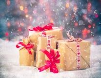 Τα πακέτα παρουσιάζουν το υπόβαθρο Χριστουγέννων χρωμάτισαν το χιόνι s δώρων φω'των στοκ εικόνες