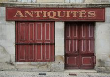Τα παλαιά γαλλικά έκλεισαν με παντζούρια το μέτωπο καταστημάτων στο κόκκινο στοκ φωτογραφίες