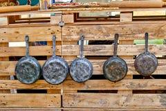 Τα παλαιά δοχεία σιδήρου και τα παλαιά τηγανίζοντας τηγάνια κρεμούν στους γάντζους παλαιά εργαλεία κουζινώ Στοκ Εικόνες