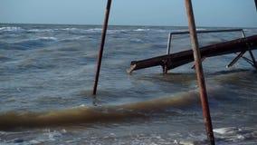Τα παλαιά, σπασμένα, περίπτερα, awnings, πλημμύρισαν με το νερό στην παραλία Τα μικρά κύματα της λασπώδους θάλασσας, που χύνονται απόθεμα βίντεο