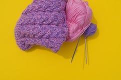 Τα παλτά του ροζ και της πορφύρας μαλλιού βρίσκονται δίπλα σε μια αποσυνδεμένη ΚΑΠ Κίτρινη ανασκόπηση στοκ εικόνες