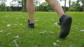 Τα παπούτσια ατόμων ικανότητας κλείνουν επάνω να τρέξουν στη χλόη απόθεμα βίντεο