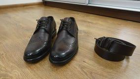 Τα παπούτσια ατόμων ` s είναι στο πάτωμα δίπλα στην κουρτίνα, εξαρτήματα ατόμων ` s Στοκ Εικόνα