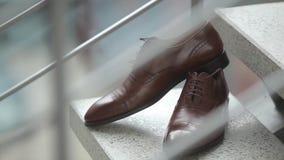 Τα παπούτσια ατόμων ` s του νεόνυμφου στέκονται στα βήματα στη ημέρα γάμου πριν από τη σοβαρή τελετή φιλμ μικρού μήκους