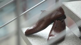 Τα παπούτσια ατόμων ` s του νεόνυμφου στέκονται στα βήματα στη ημέρα γάμου πριν από τη σοβαρή τελετή απόθεμα βίντεο
