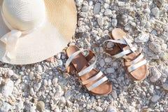 Τα παπούτσια σανδαλιών καπέλων θερινού αχύρου επίπεδος-βάζουν τις παραθαλάσσιες διακοπές στοκ φωτογραφία