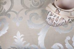 Τα παπούτσια των γυναικών με ένα τόξο σε ένα υπόβαθρο του εκλεκτής ποιότητας υφάσματος κλείνουν Στοκ Εικόνα