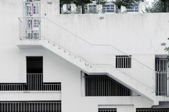 Τα παράθυρα καγκέλων των διαφορετικών μορφών και των μεγεθών στον άσπρο συμπαγή τοίχο, μια εξωτερική σκάλα στο κτήριο, κάλυψαν το Στοκ φωτογραφία με δικαίωμα ελεύθερης χρήσης