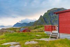 Τα παραδοσιακά κόκκινα σπίτια στρατοπέδευσης με μια όμορφη θάλασσα βλέπουν δίπλα στο χωριό Α μέσα, Νορβηγία Στοκ Φωτογραφίες
