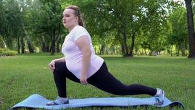 Τα παχύσαρκα τεντώματα κοριτσιών στο πάρκο, καθημερινή ρουτίνα για την απώλεια του βάρους, επιθυμούν να είναι λεπτά στοκ εικόνες