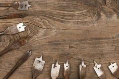 Τα παλαιά κομμάτια φτυαριών μετάλλων για τη διάτρυση του ξύλου βρίσκονται ξύλινο υπόβαθρο Στοκ Φωτογραφία