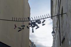 Τα παλαιά παπούτσια κρεμούν στα σιδερόβεργα Στοκ Φωτογραφίες