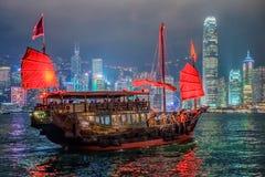 Τα παλιοπράγματα Χονγκ Κονγκ που πλέουν τη νύχτα με το υπόβαθρο ουρανοξυστών σε Tsim Tsim Sha Tsui από το λιμάνι Βικτώριας στοκ φωτογραφίες με δικαίωμα ελεύθερης χρήσης